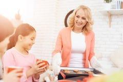 Печенья выпечки Красивая бабушка с ее внуками печет печенья в кухне стоковое изображение rf