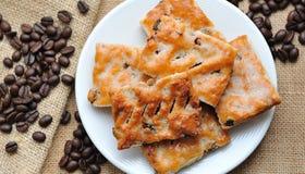 Печенья в белой плите с кофейными зернами на коричневом холсте Стоковые Фото