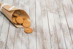 Печенья в бумажной сумке на белой деревянной предпосылке установьте текст Стоковые Фотографии RF