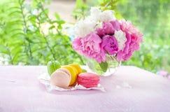 Печенья желтого цвета макарон, красного цвета, зеленого цвета, и цветков пинка на предпосылке букета пионов Стоковые Изображения RF