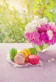 Печенья желтого цвета макарон, красного цвета, зеленого цвета, и цветков пинка на предпосылке букета пионов Стоковая Фотография