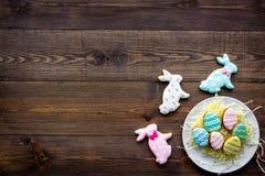Печенья зайчика пасхи и пасхальных яя Символы и традиции пасхи Темный деревянный космос экземпляра взгляд сверху предпосылки Стоковые Фотографии RF