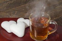 Печенья имбиря в форме политых сердца и горячего чая низкий ключ, селективный фокус Стоковая Фотография RF