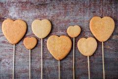 Печенья имбиря на ручке в форме сердец выровнялись вверх на wo Стоковое Изображение RF
