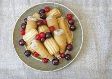 Печенья и вишни на плите взгляд сверху Стоковые Фото
