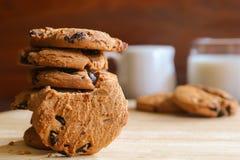 Печенья и молоко обломоков шоколада на деревянной предпосылке Стоковые Изображения RF