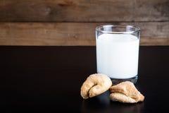 2 печенья и стекла молока на черной таблице против старого woode Стоковые Фото