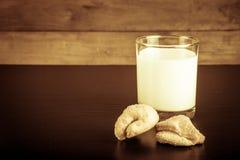 2 печенья и стекла молока на черной таблице против старого woode Стоковые Фотографии RF