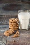 Печенья и стекло молока на деревенской деревянной предпосылке Стоковое Фото