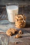 Печенья и стекло молока на деревенской деревянной предпосылке Стоковые Фотографии RF