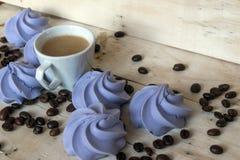 Печенья и чашка кофе меренги французской сини на деревянной предпосылке Стоковые Изображения