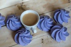 Печенья и чашка кофе меренги французской сини на деревянной предпосылке Стоковая Фотография