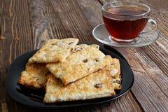 Печенья и чашка чаю на деревянном столе темного коричневого цвета Стоковая Фотография