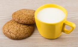 2 печенья и чашки молока на таблице Стоковые Изображения