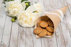 Печенья и pionies цветут на белой деревянной предпосылке установьте текст Стоковое Изображение
