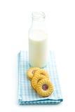 Печенья кольца варенья и бутылка молока Стоковые Изображения