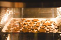 Печенья Кристмас в печи Стоковые Изображения