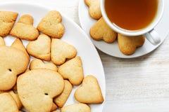 Печенья крупного плана в форме сердц и чашка чаю Стоковые Фотографии RF