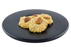 Печенья миндалины на черном блюде с путем клиппирования Стоковое Изображение RF