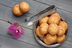 Печенья миндалины с схватами и орхидеей сахара цветут на деревенском деревянном столе Стоковое Изображение
