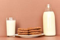 Печенья на белых плите и молоке в стеклянной бутылке и прозрачном стекле стоковое изображение