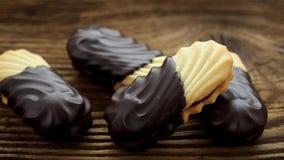 Печенья на деревянном столе Печенья с заполнять на деревянном столе Сладостные печенья окунутые в шоколаде сток-видео