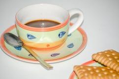 Печенья на поддоннике с предпосылкой белизны кофейной чашки стоковые изображения rf