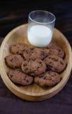 Печенья обломока шоколада на темной предпосылке с стеклом молока Стоковые Фотографии RF