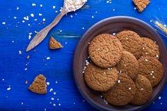 Печенья овсяной каши в коричневой плите на голубой предпосылке Деревенский тип Взгляд сверху Стоковая Фотография RF