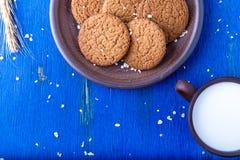 Печенья овсяной каши в коричневой плите около чашки молока на голубой предпосылке Деревенский тип скопируйте космос Взгляд сверху Стоковые Фотографии RF