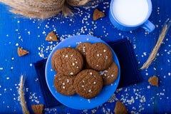Печенья овсяной каши на голубой плите в чашке молока деревенский Взгляд сверху Стоковые Фото