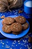 Печенья овсяной каши на голубой плите в чашке молока деревенский Стоковое фото RF