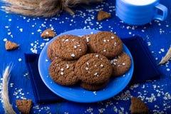 Печенья овсяной каши на голубой плите на голубой деревянной предпосылке Печенья овса с чашкой молока Стоковая Фотография RF
