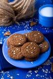 Печенья овсяной каши на голубой плите на голубой деревянной предпосылке Печенья овса с чашкой молока Стоковое Изображение RF