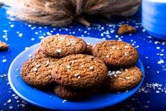 Печенья овсяной каши на голубой плите на голубой деревянной предпосылке Печенья овса с чашкой молока Стоковые Фотографии RF