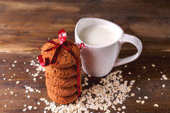 Печенья овсяной каши на предпосылке овсов, рядом с стеклом молока, на винтажной доске Стоковая Фотография