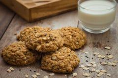 Печенья овсяной каши с семенами сезама и стеклом молока Стоковые Изображения RF