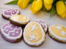 Печенья пасхального яйца форменные и желтые тюльпаны Стоковое Изображение
