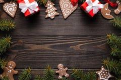 Печенья, подарки, елевое дерево и украшения на деревянном столе стоковое фото rf