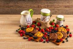 Печенья, поленики и плоды леса помещенные на деревянном диске стоковое изображение