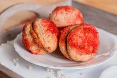 Печенья при сливк клубники покрытая с брызгают o, красные круглые печенья на подносе, чашку чаю на деревянной предпосылке, валент Стоковое фото RF
