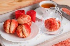 Печенья при сливк клубники покрытая с брызгают o, красные круглые печенья на подносе, чашку чаю на деревянной предпосылке, валент Стоковое Изображение