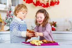 Печенья пряника выпечки мальчика и девушки ребенк Littlke Стоковое Изображение RF