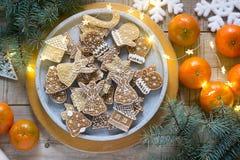Печенья пряника на конкретном подносе на предпосылке зимы с tangerines, ветвями ели и гирляндой стоковые фотографии rf
