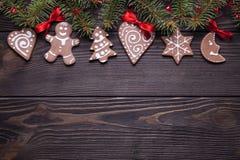 Печенья рождества, елевое дерево и красные смычки на деревянном столе стоковое изображение rf