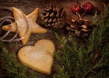Печенья рождества, ветвь сосны и pinecones на древесине Стоковые Изображения