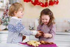 Печенья рождества выпечки мальчика и девушки дома Стоковая Фотография