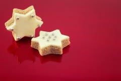 2 печенья рождества звезды на красной предпосылке, как backgro Xmas Стоковое Изображение