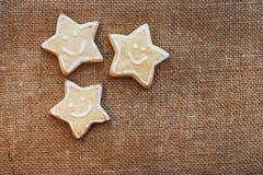 3 печенья рождества на текстуре льна Стоковые Изображения