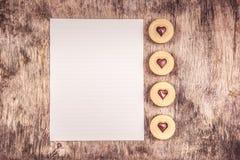 печенья романтичные Печенья сердца с шоколадом и чистым листом бумаги на деревянной предпосылке Стоковая Фотография RF